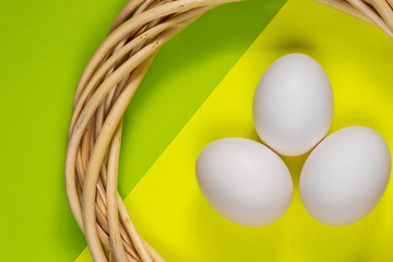 chicken eggs in a round wreath of wicker tree branches on an isolated green-yellow background