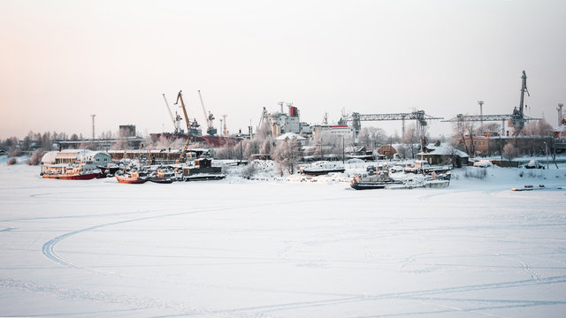 The ships, cranes and water vessels are frozen in the port. Winter cold day at the river port. Gray sky and frozen river. Everything is covered with snow