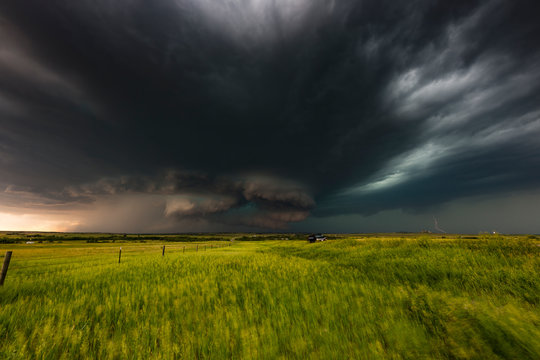 A dramatic supercell thunderstorm over green grass.