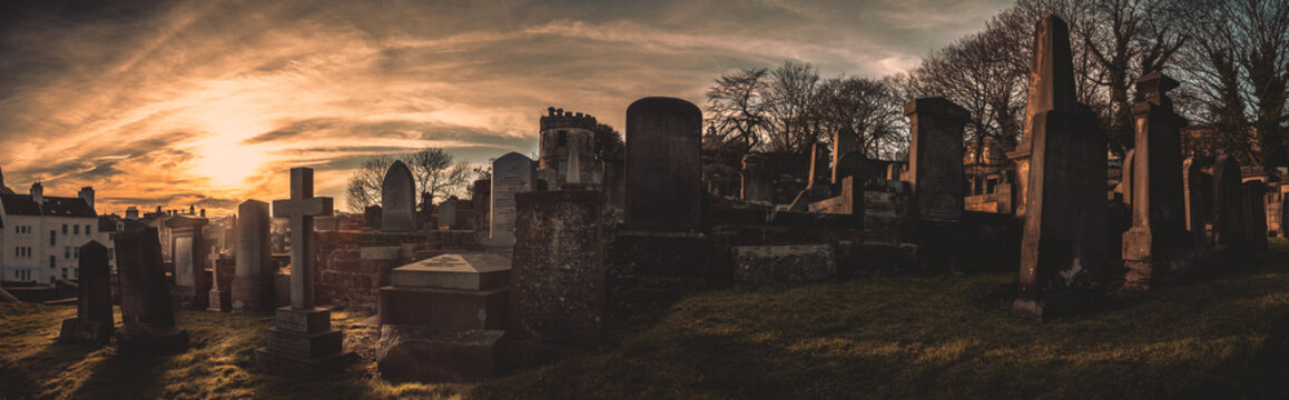 EDINBURGH, SCOTLAND DECEMBER 14, 2018: old, desolated and grungy tombstones, memorials and headstones in the graveyard with the sun rising at New Calton Burial Ground