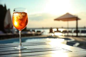 Glass of fresh summer cocktail on wooden table near swimming pool outdoors at sunset. Space for text