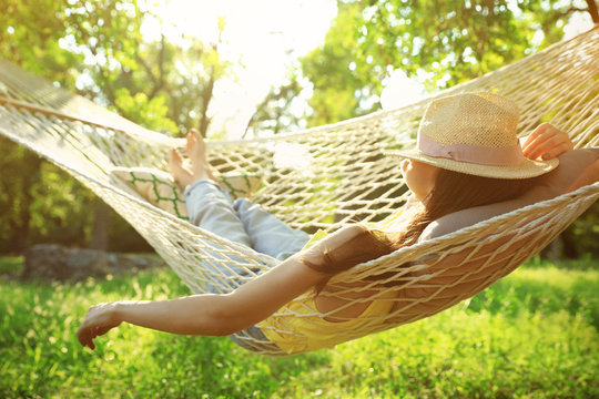 Young woman with hat resting in comfortable hammock at green garden