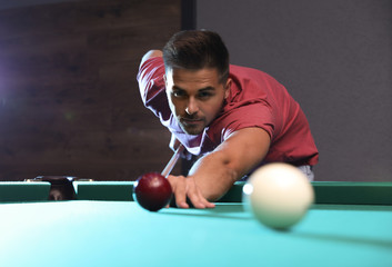 Handsome young man playing Russian billiard indoors