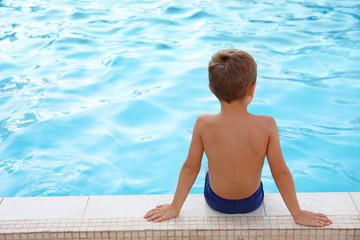 Cute little boy sitting near outdoor swimming pool