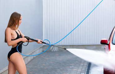 Young woman in swimsuit with high pressure water jet cleaning automobile at car wash