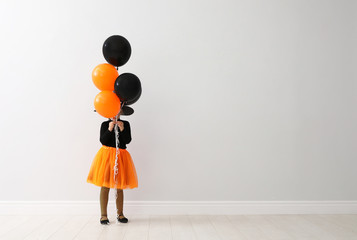 Cute little girl with balloons wearing Halloween costume near light wall. Space for text Wall mural