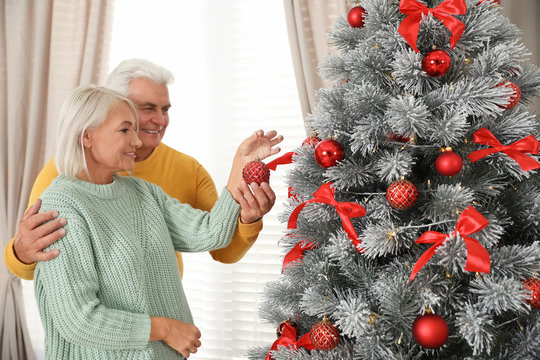 Happy mature couple decorating Christmas tree at home
