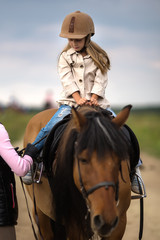 Little girl in an equestrian helmet riding a horse. Girl on a horse walk in nature.