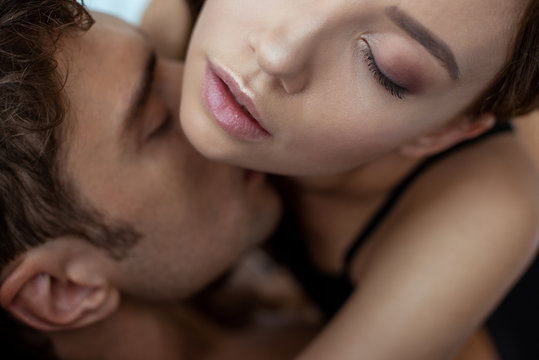 top view of man with closed eyes kissing sexy woman
