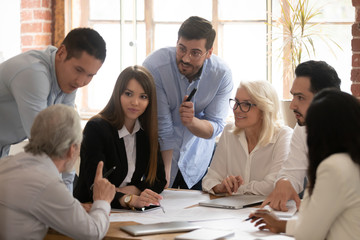 Motivated diverse businesspeople brainstorm at office meeting