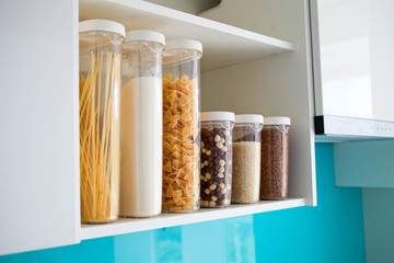 Stocked kitchen pantry with food - pasta, buckwheat, rice and sugar , side view.