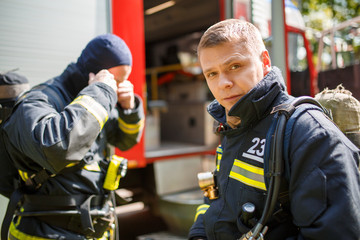 Two men firefighters standing near fire engine in afternoon,