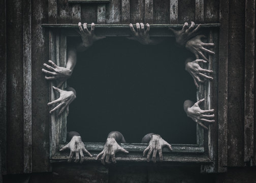 Hands rising out from the old window ancient house, Halloween concept. Increased noise and grain effect.