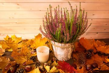 Obraz Kompozycja wrzos ze świeczką na jesiennych liściach - fototapety do salonu