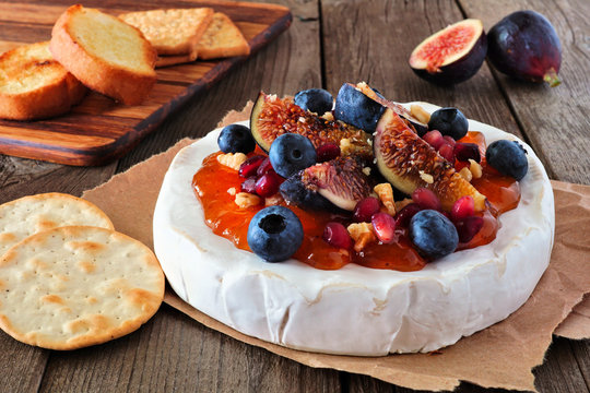 Baked brie appetizer with figs and jam, blueberries, pomegranates and nuts. Side view on a rustic wooden table.