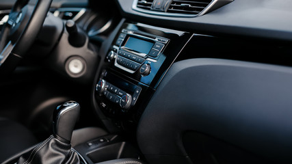 Car detailing. Dashboard. Media, climate and navigation control buttons. Sound system. Modern car interior details.