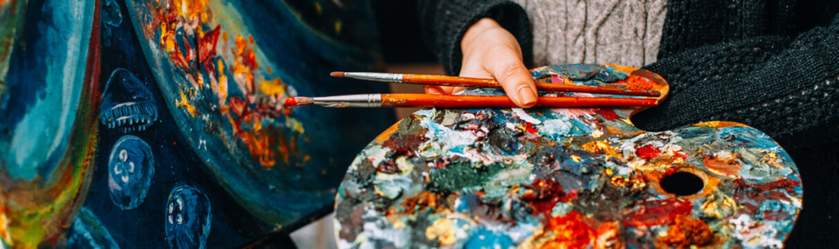 Modern fine art school. Female painter holding colorful palette and paintbrushes over abstract artwork.