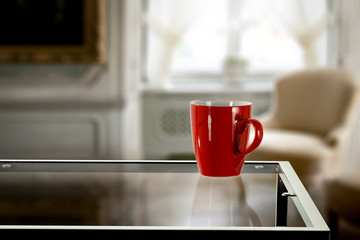 Fototapete - Red mug on glass coffee table and free space for your decoration