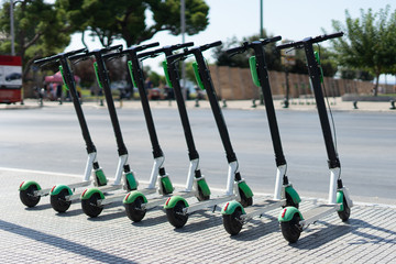 Lime Electric push kick scooter sharing rentals in sunny day by in a row scooters by the street on the sidewalk in a city thessaloniki ready to ride or rent