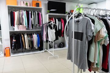 The wardrobe fashion clothes of various brands. Сloset in which everything put in order. All things are folded neatly. Everything is in its place. Harmony. Showroom.