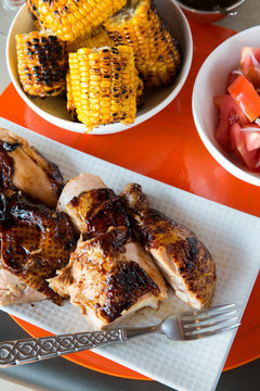 Rotisserie chicken, grilled yellow corn and tomatoe salad.