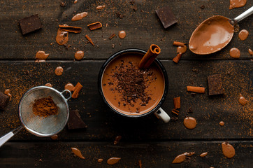 cup of hot chocolate on black wooden boards with drops of chocolate, cocoa