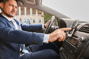 Businessman using mobile phone for navigation while driving car