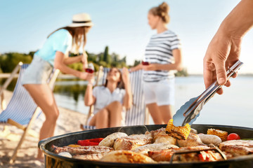 Man cooking tasty food on barbecue grill outdoors, closeup