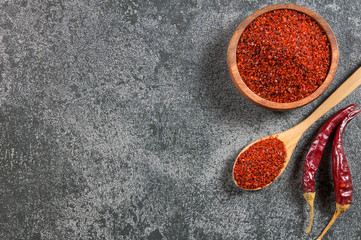 Canvas Prints Hot chili peppers Top view red dried crushed hot chili peppers and chili flakes or powder in wooden spoon and bowl on grey rustic background, healthy turkish spice