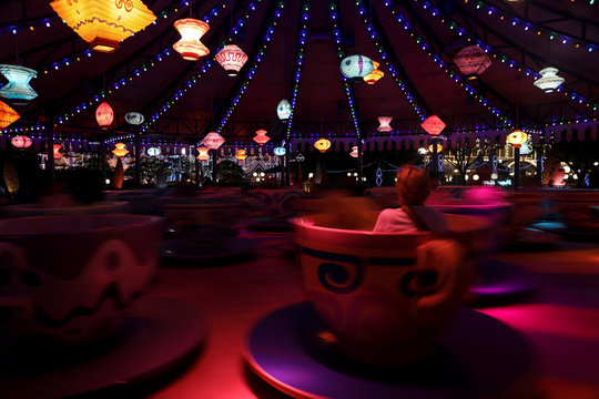 A handful of people enjoy the Mad Hatter Tea Cups an hour before closing time in Hong Kong Disneyland in Hong Kong