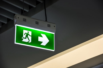 Illuminated green emergency exit sign hanging on ceiling in modern building