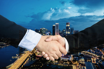 double exposure, cooperation or partnership business shaking hand with partnership after making profitable agreement with singapore city in background. Smart man handshake, deal and greeting concept.