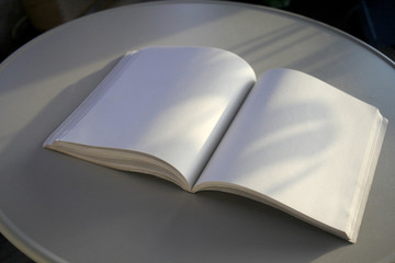 open book with blank pages with light and shadows on cream table