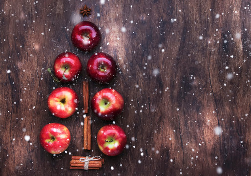 Creative Christmas tree made from red apples, cinnamon and anise star on wooden brown background