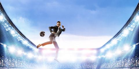 Business woman playing footbal on stadium