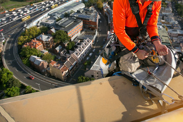 Close up pic of certifies rope access high rise worker abseiler using yellow ascender descending with low stretch abseiling rope over the edge from high rise roof building construction site, Sydney