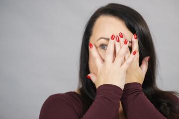 Woman peeking through her hands