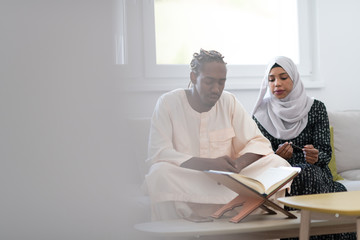 african couple at home reading quaran