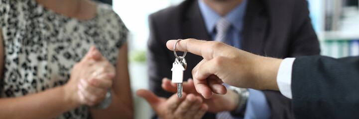 Focus on male hand holding bunch of keys. Joyful couple looking at estate agent with happiness and clapping. Buying property concept. Blurred background