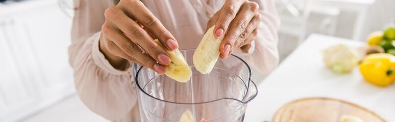 panoramic shot of woman putting sliced bananas into blender