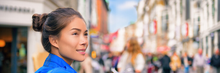 Tourist travel Asian woman walking on city street looking at shops visiting Europe. Banner panorama lifestyle.