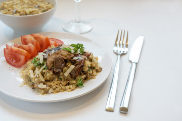 low carb risotto made from cauliflower with porcini mushrooms, parsley, parmesan and tomatoes on a plate, white table, copy space