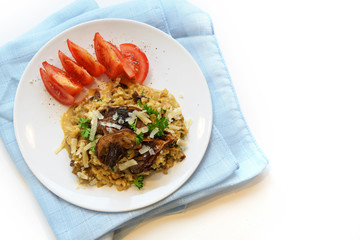 creamy risotto from cauliflower with porcini mushrooms and tomatoes on a plate and a blue napkin, background with copy space is fading to white, top view from above