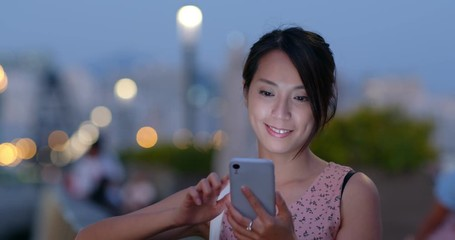 Wall Mural - Young woman use smart phone in evening time