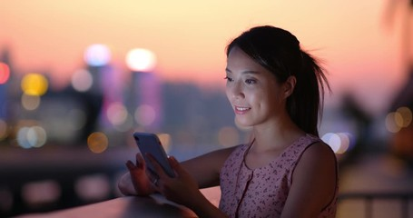 Wall Mural - Young woman use smart phone at sunset