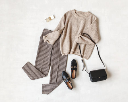 Brown pants in check, beige knitted oversize sweater, cross body bag, black loafers or flat shoes on grey background. Overhead view of women's casual day outfit. Flat lay, top view. Women clothes.