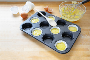 muffin tin, partly filled with paper cups and dough for cupcake baking on a wooden kitchen table, copy space