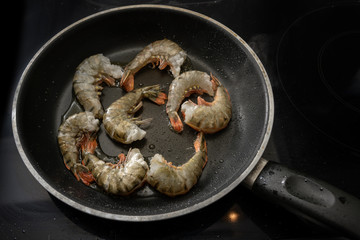roasting raw black tiger prawn shrimps with shell but without head in a pan on the stove, cooking a tasty meal for low carb diet
