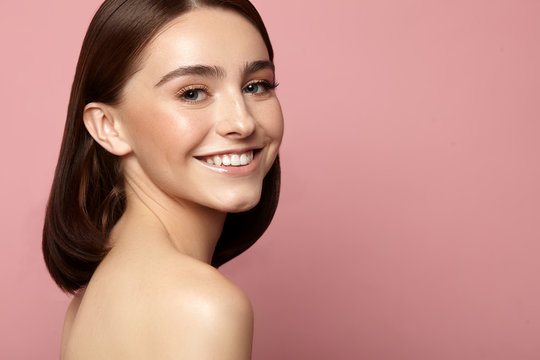 Beautiful smiling woman with clean skin, natural makeup and white teeth on a pink background