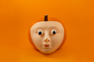 Halloween pumpkin with eyes stock images. Halloween pumpkin with eyes and scary mask. Creepy halloween pumpkin on a orange background. Plastic human mask on pumpkin. Halloween plastic white face mask